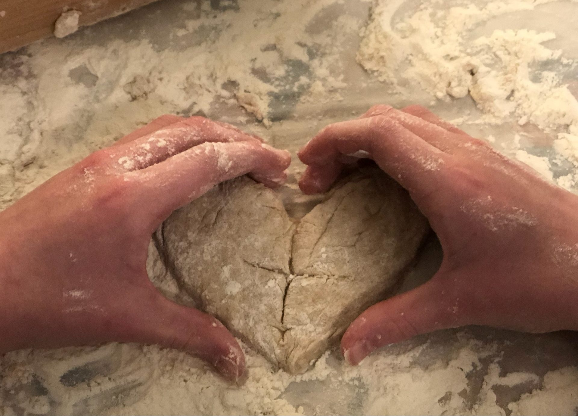 Hands in a heart shape wrapped aroung a heart shaped losf of bread with a cross on it