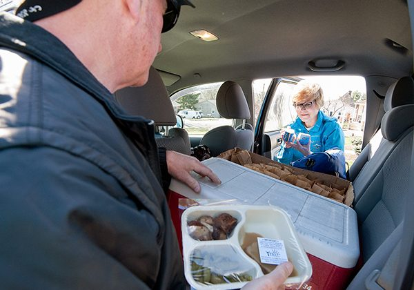 A man and woman are loading meals into theor car for delivery